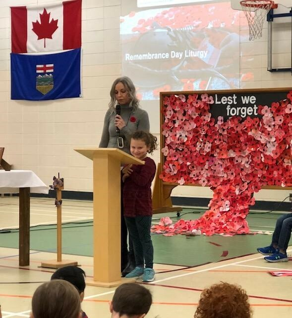 Kerrie Fedunyk, grade 2 teacher accompanies Kali, student at Albert Lacombe Catholic School to begin their assembly with the Treaty Six Acknowledgment
